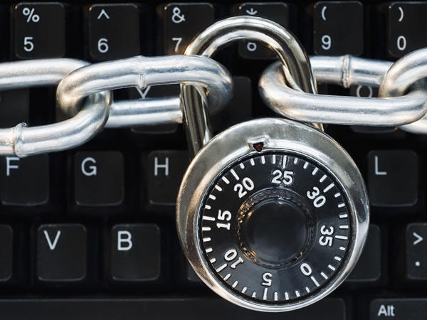 Close-up of a computer keyboard behind a padlock and chain.